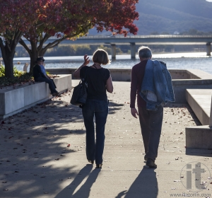 Autumn. Couple walks along embankment of Burley Griffin Lake near National Gallery. Canberra. Australia