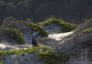 Man walks on sand dunes. Fingal Bay. Port Stephens. Australia.