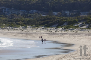 Two couples walk on a beach. Fingal Bay. Port Stephens. Australia.