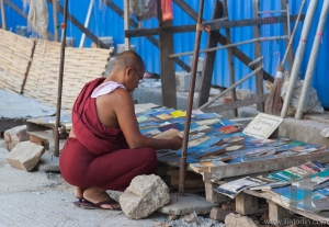 Buddhist monk choosing book on street market. Yangon. Myanmar.