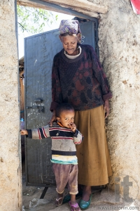Grandmother with grandchild posing in the entrance of their house in ancient walled city of Jugol, that daily life is almost unchanged in more than four hundred years. Harar. Ethiopia.