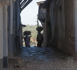 HARAR, ETHIOPIA - DECEMBER 23, 2013: Unidentified women carry things on their heads in narrow alleyways of ancient city of Jugol.
