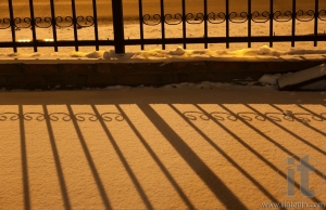 Shadow of fence on snow in orange street light at night. Russia.