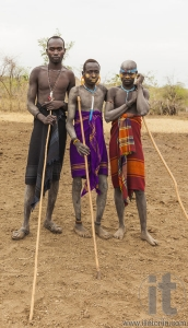 Boys and a man from Mursi tribe with spears in Mirobey village.