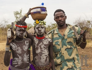 Boys from Mursi tribe and a solder with machine guns in Mirobey