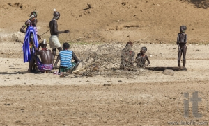 Hamar men teach hunting young boys on a dry river bed.