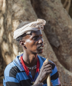 Traditionally dressed Hamar man with chewing stick in his mouth.